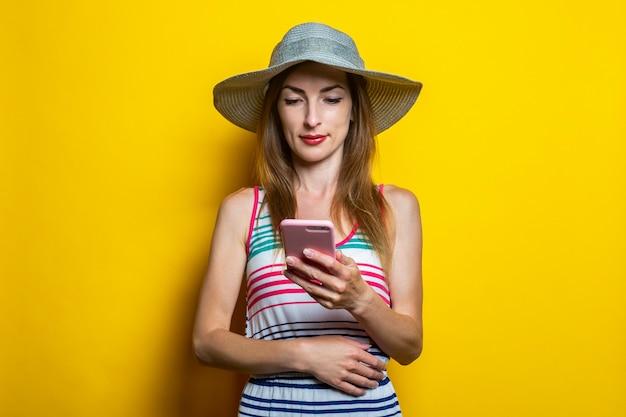縞模様のドレスと携帯電話を見て帽子の少女