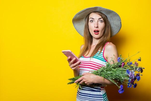 携帯電話を持って花と帽子の驚いたショックを受けた少女