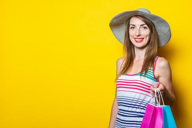 Молодая женщина в шляпе и полосатом платье улыбается, держит пакеты с покупками