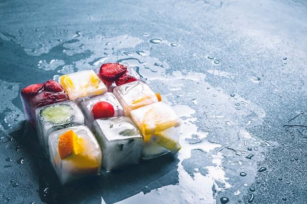 石の青い表面にフルーツのアイスキューブ。正方形の形状。ミント、イチゴ、チェリー、レモン、オレンジ。フラット横たわっていた、トップビュー