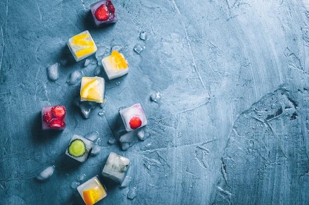 フルーツと砕いた氷と石の青い表面のアイスキューブ。ミント、イチゴ、チェリー、レモン、オレンジ。フラット横たわっていた、トップビュー