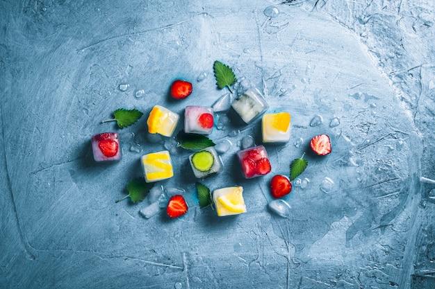 Кубики льда с фруктами и сломанный лед на камне синей поверхности. мята, клубника, вишня, лимон, апельсин. плоская планировка, вид сверху