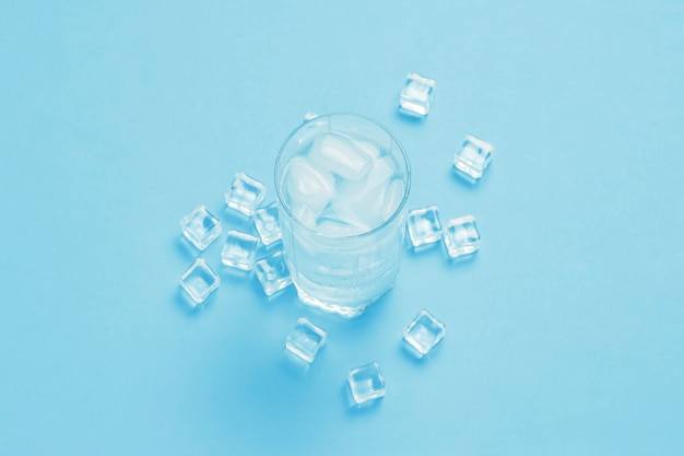 Стакан освежающей холодной воды со льдом и кубиками льда на синей поверхности.