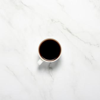大理石のテーブルの上のコーヒーカップ。コンセプトの朝食、ブラックコーヒー、夜のコーヒー、不眠症。フラット横たわっていた、トップビュー
