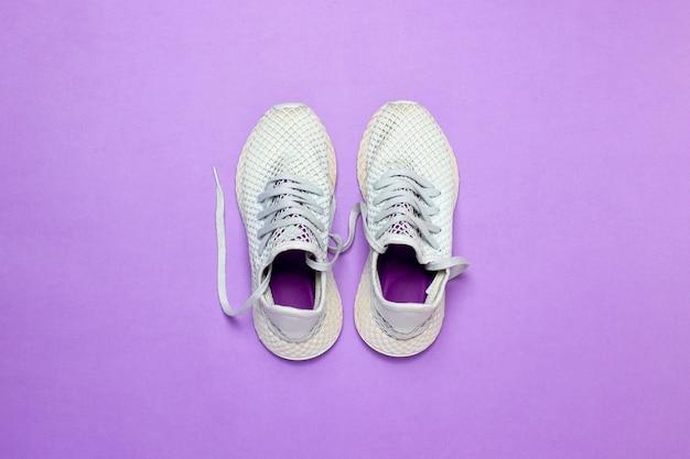 紫色の表面に白いランニングシューズ。ランニング、トレーニング、スポーツの概念。 。フラット横たわっていた、トップビュー