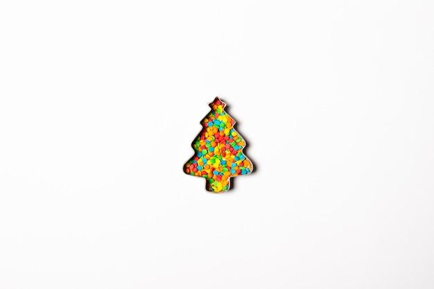 Форма рождественской елки и пестротканые украшения на светлой поверхности. , рождество, новогодняя концепция. минимализм. плоская планировка, вид сверху