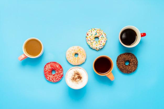 おいしいドーナツとカップと青い表面のホットドリンク。お菓子、ベーカリー、ペストリー、コーヒーショップ、友人、フレンドリーなチームの概念。フラット横たわっていた、トップビュー