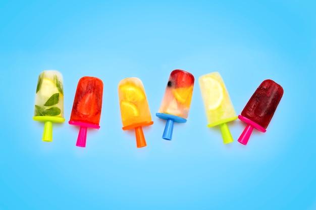 青い表面に自家製の健康的なフルーツアイスキャンデー。