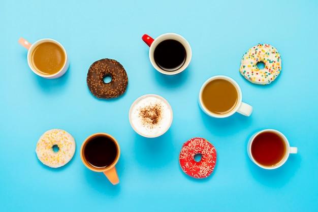 おいしいドーナツとカップ、ホットドリンク、コーヒー、カプチーノ、青い表面のお茶。お菓子、ベーカリー、ペストリー、コーヒーショップ、会議、友人、フレンドリーなチームの概念。フラット横たわっていた、トップビュー