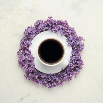 Чашка с кофе на блюдце, в окружении сиреневых цветов на поверхности