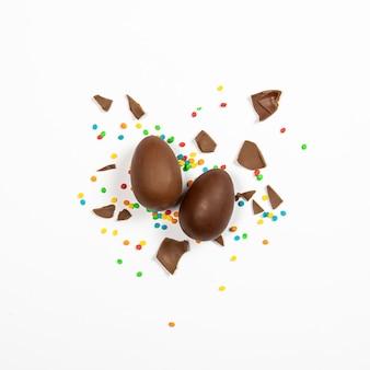 Пасхальные шоколадные яйца и красочные украшения на светлой поверхности. пасхальная концепция, пасхальные угощения. площадь. плоская планировка, вид сверху