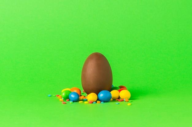 緑の表面にイースターチョコレートの卵とマルチカラーのお菓子。メリーイースターのお祝いのコンセプト。
