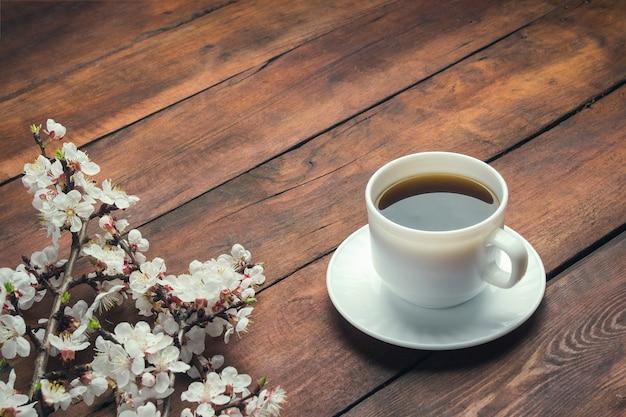 桜の木の枝と暗い木製の表面にブラックコーヒーと白いカップ。春の概念