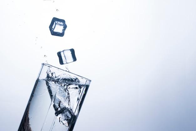 Всплеск воды в стакан из кубика льда.