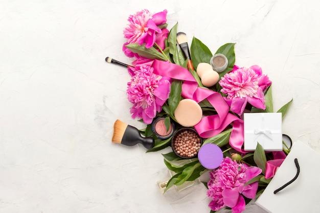 Подарочная белая упаковка, подарочная упаковка, декоративная косметика, розовая лента и розовые пионы. вид сверху.