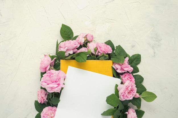 明るい石の表面に黄色のカバーが付いた本の周りにピンクのバラが並んでいます。愛とロマンス小説に関する本のコンセプト。フラット横たわっていた、トップビュー