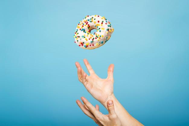 Руки ловят пончик с глазурью. концепция выпечки, ручной работы. плоская планировка, вид сверху