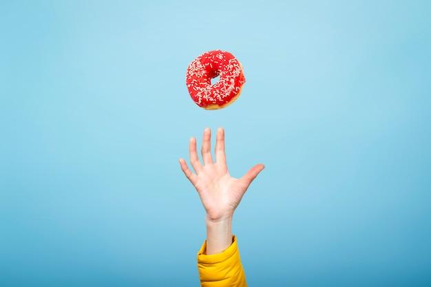 Рука поймать пончик с красной глазурью. концепция выпечки, ручной работы. плоская планировка, вид сверху