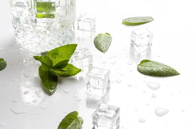 Пролитое стекло с освежающей водой, листьями мяты и кубиками льда на белой поверхности. плоская планировка, вид сверху