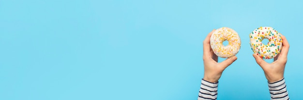 Женские руки держат пончики на синем. концепт кондитерский магазин, выпечка, кофейня.