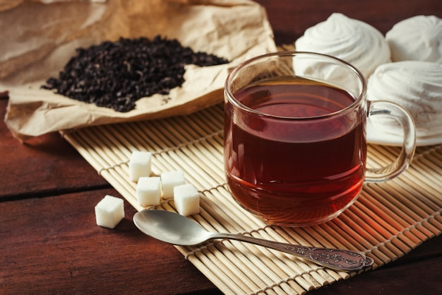 Чашка с чаем, сушеные чайные листья на крафт-бумаге, сахар и ложка сахара на деревянном столе
