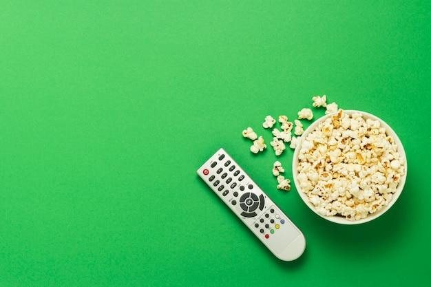 ポップコーンのボウルと緑の背景にテレビのリモコン。テレビ、映画、テレビシリーズ、スポーツ、ショーを見るの概念。