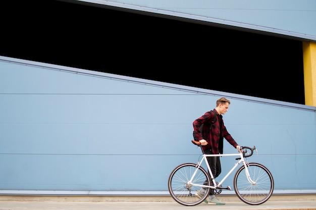 スタイリッシュな若者が青い壁の前に白い自転車で歩く