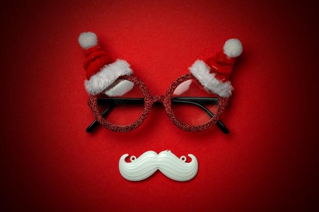 サンタのメガネと白いヒップスター口ひげと赤のクリスマス背景。