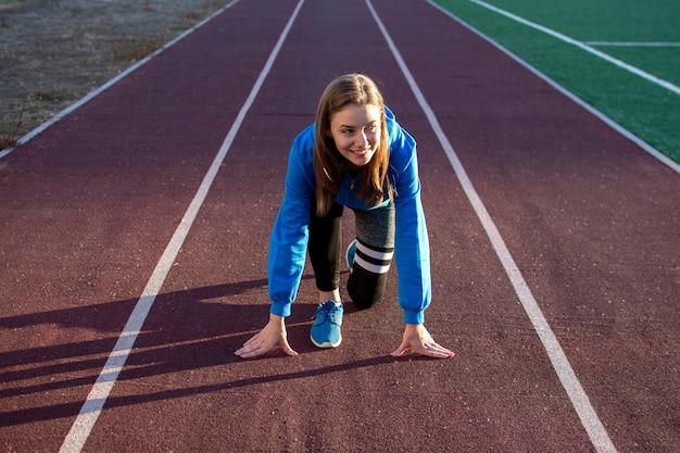 若い女の子がトレッドミルで開始時に立っている、路上で女性ランナー運動