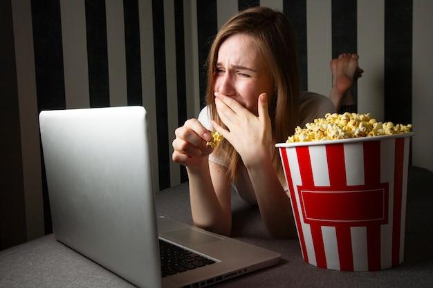 Молодая девушка смотрит телевизионное шоу ночью в ноутбуке и ест попкорн, она использует компьютер, лежа на диване