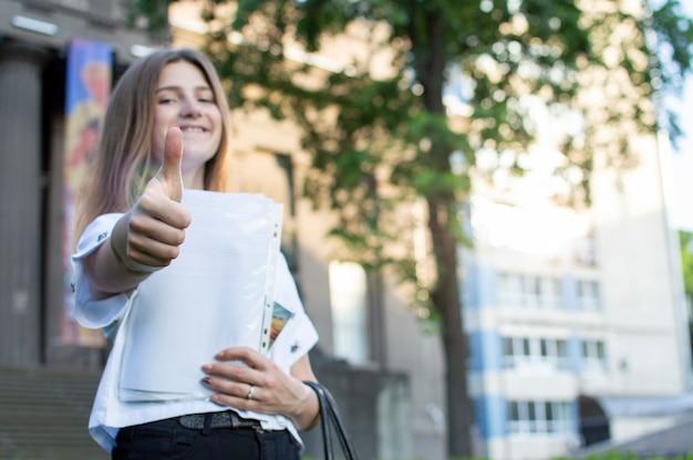 Молодая студентка стоит возле университета, держит в руках газету, улыбается и показывает, как против колледжа, она идет в школу
