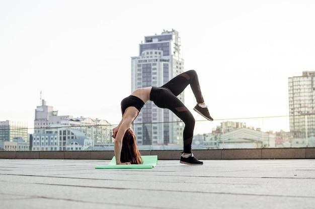 都市の背景に体操をしている女の子
