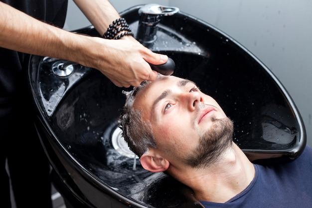 Парикмахер, моющий волосы клиентов