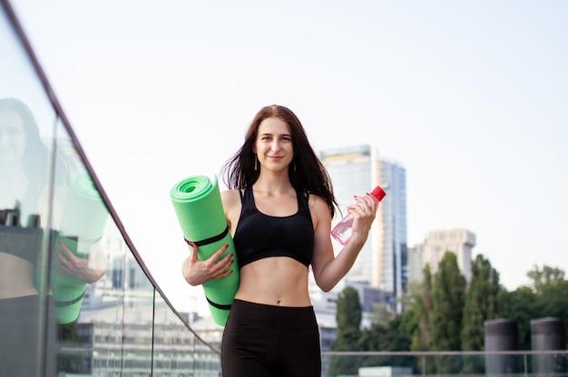 Спортивная девушка занимается йогой по утрам на улице