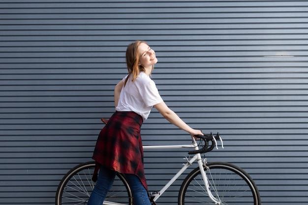 白い自転車で立っている若い女の子