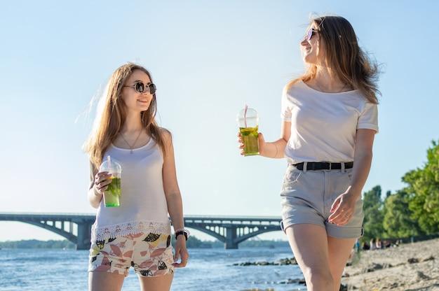 モヒートと一緒にビーチを歩く若い女の子