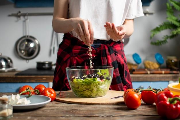 若い女の子は、キッチンでベジタリアンサラダを準備します