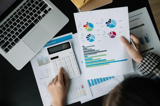 金融、税、会計、統計、分析研究の概念を計算するために電卓とラップトップを使用して実業家を閉じる