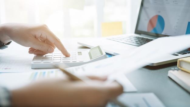 実業家と金融、税、会計、統計、分析研究の概念を計算するための計算機とラップトップを使用してパートナーを閉じる