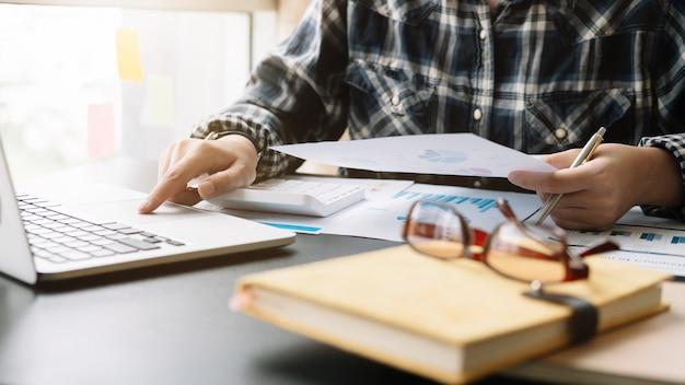 金融、税、会計、統計、分析研究の概念を計算するための計算機とラップトップを使用して実業家を閉じる