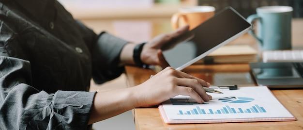 タブレットコンピューターとビジネス女性分析財務報告。