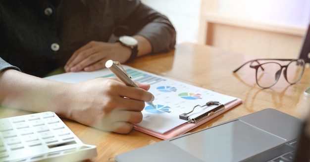 経費、会計概念を計算するために彼のオフィスで電卓で財務について働いている人を閉じる