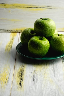 Свежие зеленые яблоки на старый деревянный стол. здоровая и экологичная еда. цветовая гармония