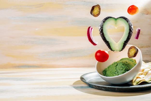 Самодельный гуакамоле чаша с ингредиентами, плавающие вокруг него. старинный деревянный стол. здоровая пища
