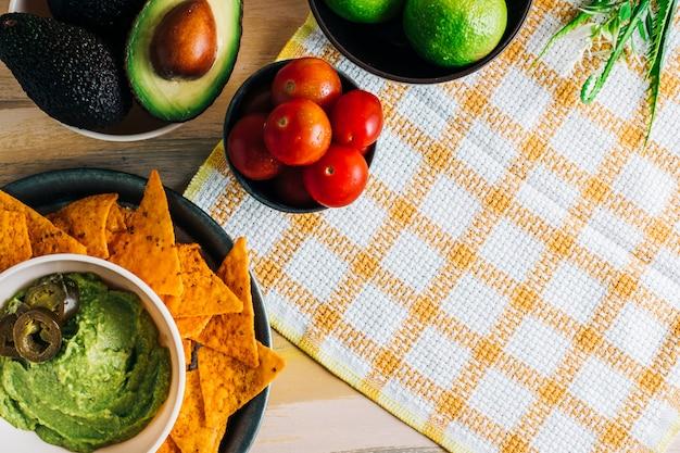 Шар гуакамоле с начос на старинный деревянный стол с свежих ингредиентов вокруг него. копировать пространство веганская еда