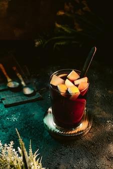 Кувшин холодной сангрии с фруктами на темной поверхности