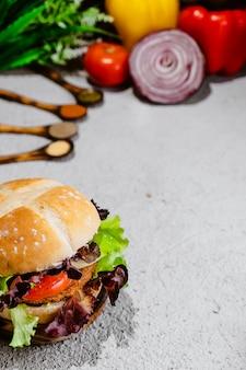 Вегетарианский бургер на деревянной поверхности с овощами. здоровая веганская еда. сейтан, соя