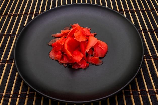 Маринованные ломтики имбиря в черной тарелке и бамбуковой циновке