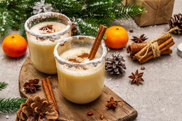 クリスマスや冬休みにシナモンとナツメグのエッグノッグ。スパイシーな縁のあるグラスで自家製の飲み物。みかん、キャンドル、ギフト。