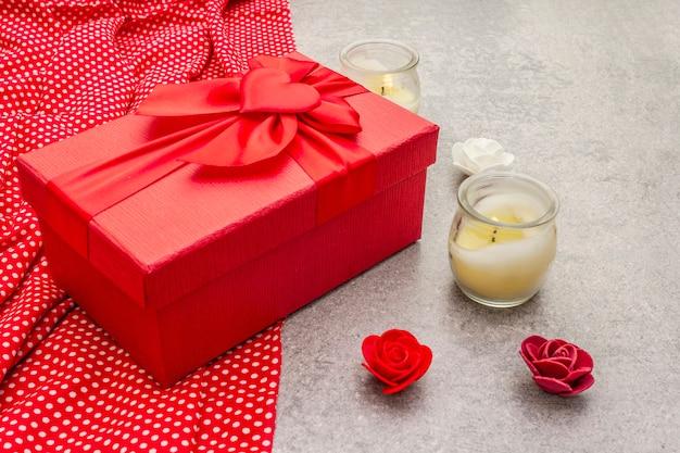 赤いギフトボックス、点線の布、キャンドル、バラとバレンタインデーの組成